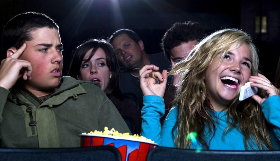 Garota conversando no celular na sala de cinema, incomodando as pessoas à sua volta.