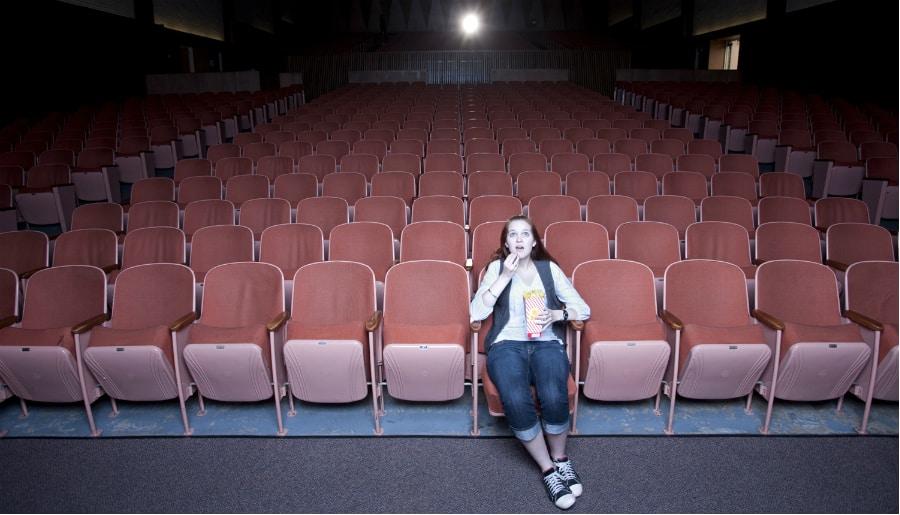 Foto de uma sala de cinema com só uma pessoa na sala