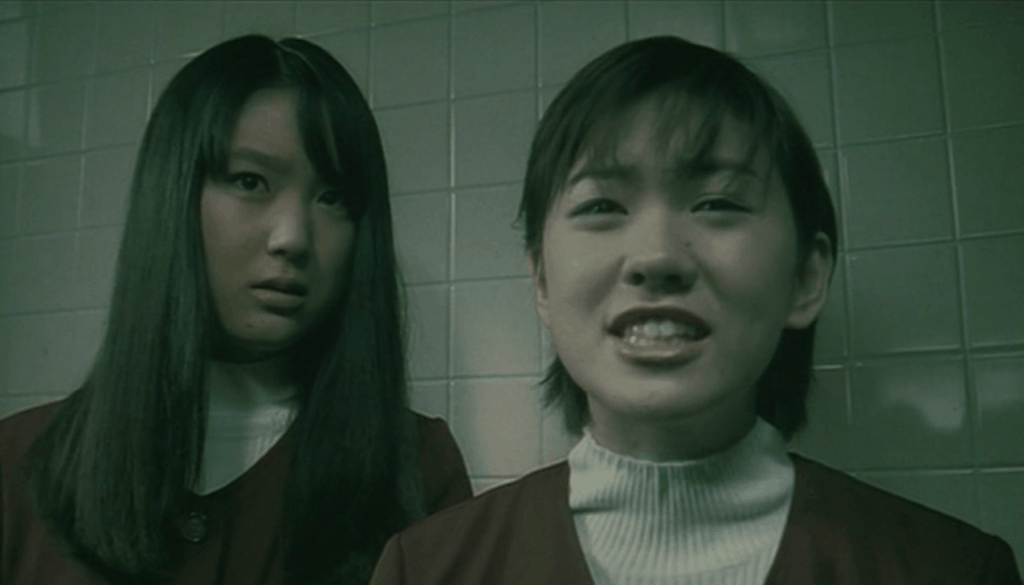 Cena do filme Uzumaki. Duas meninas aparecem lado a lado na imagem, olhando para frente.