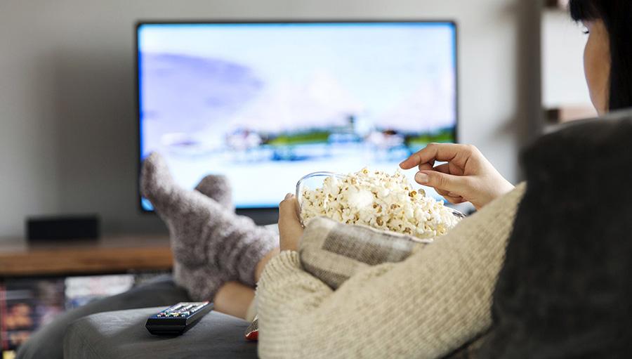 Pessoa assistindo filme em casa e comendo pipoca